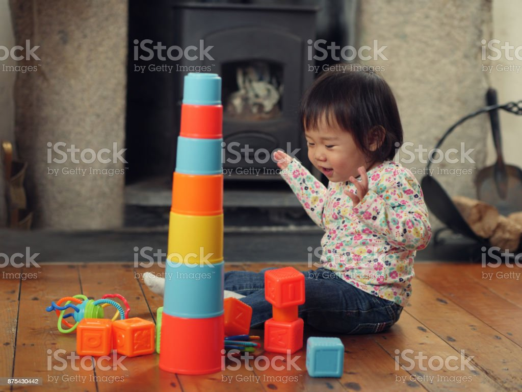 Baby girl playing toys at home stock photo
