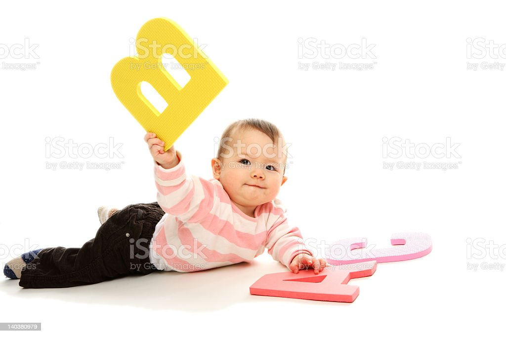 Baby girl playing with big colorful letters royalty-free stock photo