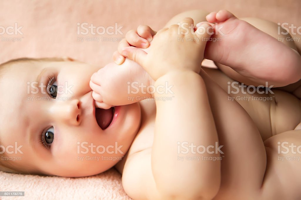Baby girl playing with her legs stock photo