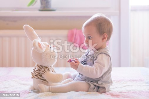istock Baby girl playing with plush rabbit 506758515