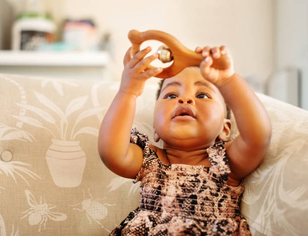 Baby girl playing with rattler toy at home stock photo