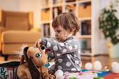 Portrait of cute one year old Caucasian baby girl with blue eyes at home, eating snack and playing with her toys