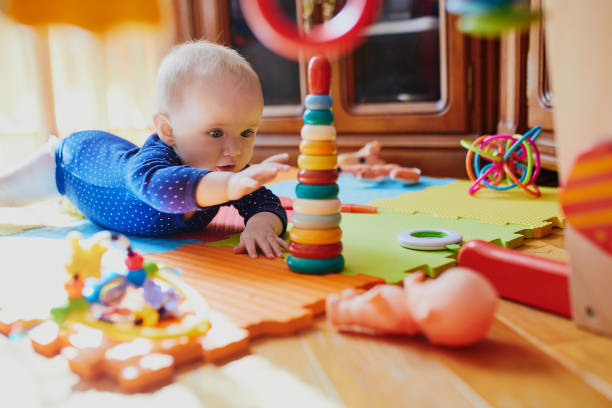 Baby girl playing with toys on the floor stock photo