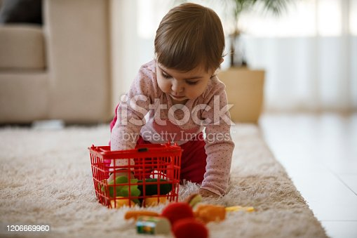 Cute black little girl embracing big teddy bear and laughing over yellow background, kids toys concept