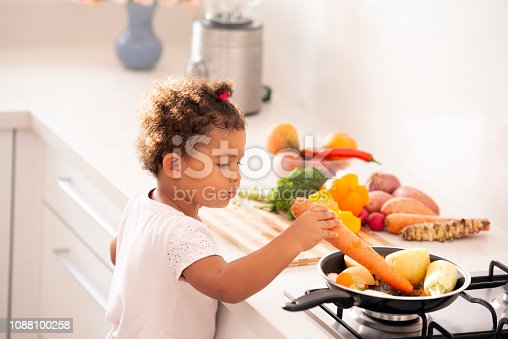 176993221istockphoto Baby girl playing with vegetables at the kitchen. 1088100258