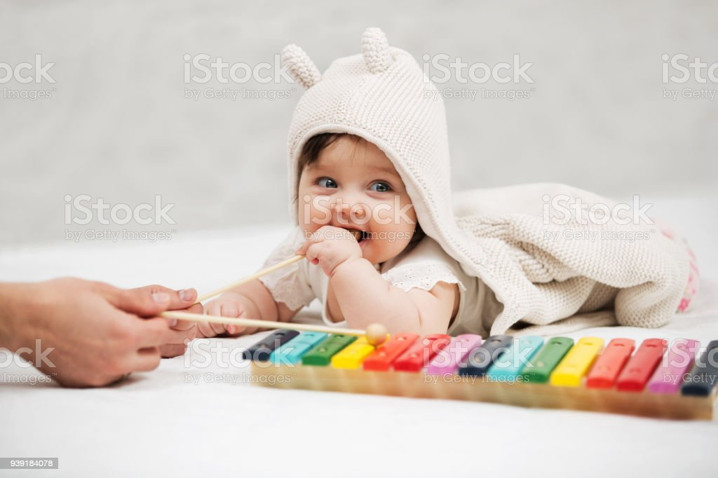 Baby girl playing with xylophone toy on blanket at home stock photo