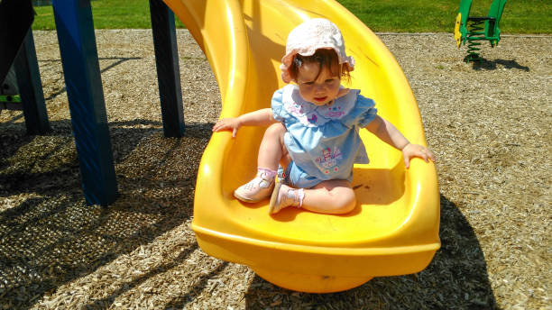 baby girl plays at the park - playpen stock pictures, royalty-free photos & images