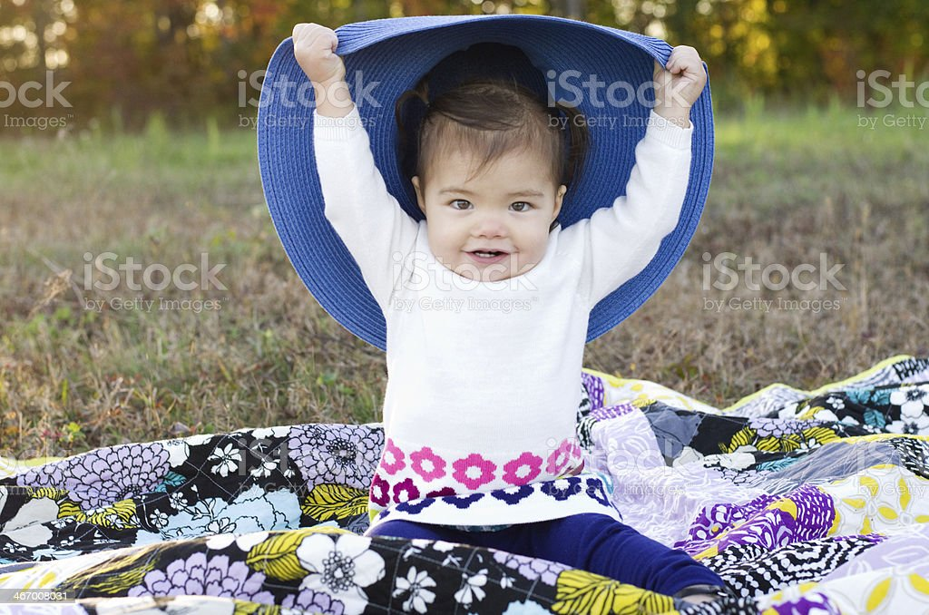 baby girl plays 'peek a boo' with large blue hat royalty-free stock photo