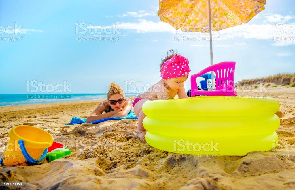 niña juega piscina inflable amarillo mamá comprueba su tomando el sol en la toalla de playa - foto de stock