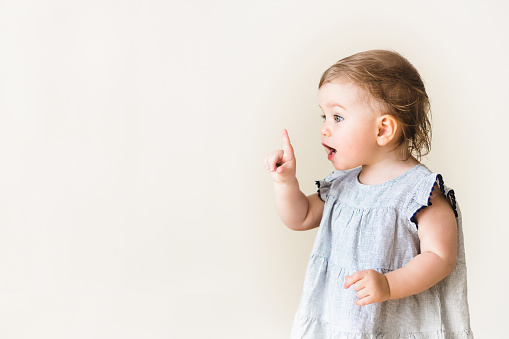 Baby girl pointing her finger, excited and emotional, on neutral background