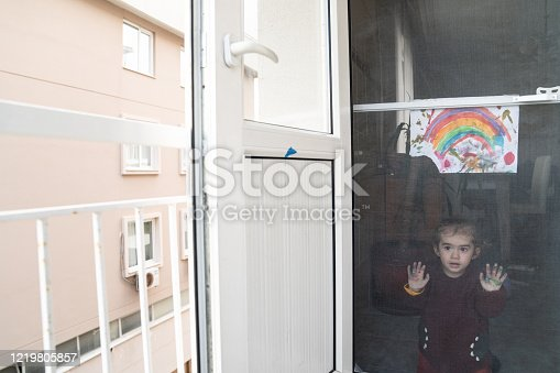 Baby girl looking through door with her watercolor painting of rainbow. Rainbow painting is known as a symbol for children locked in homes during quarantining due to covid-19 pandemy. Shot with a full frame mirrorless camera.