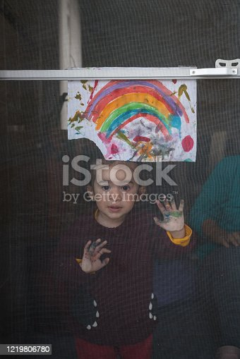 Baby girl looking through door with her watercolor painting of rainbow. Her mother is seen next to her. Rainbow painting is known as a symbol for children locked in homes during quarantining due to covid-19 pandemy. Shot with a full frame mirrorless camera.