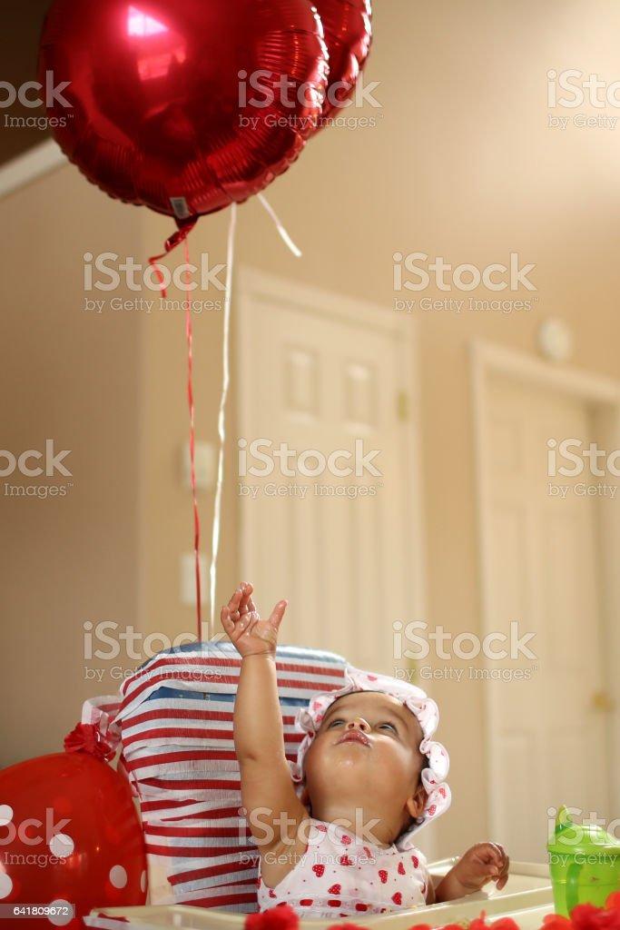 Baby girl reaching for balloon stock photo