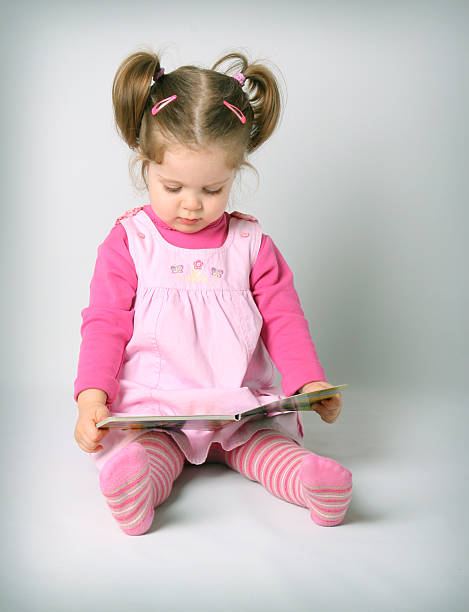 Baby girl reading book stock photo