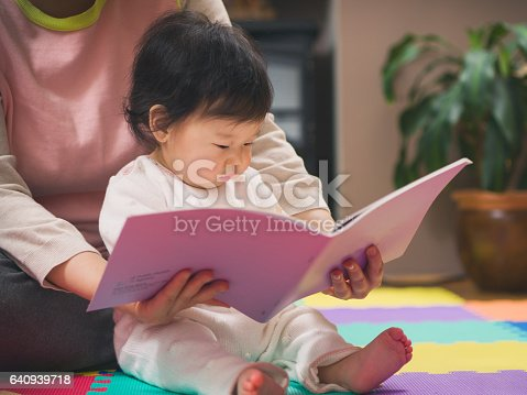 istock baby girl reading book with mom 640939718