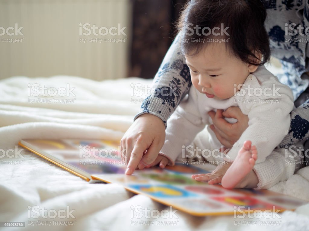 baby girl reading book with mom stock photo