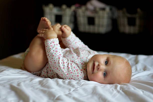 Baby Girl Relaxing and Playing with Her Toes stock photo