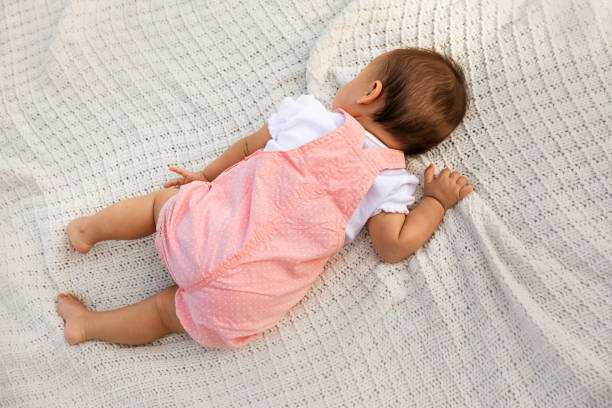 Baby girl resting on white knitted blanket, top view of infant child at natural light stock photo