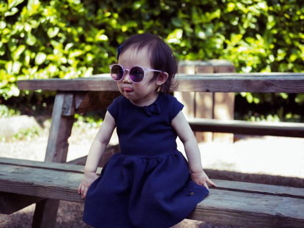 baby mädchen sitzen auf holzstuhl - sonnenbrille kleinkind stock-fotos und bilder