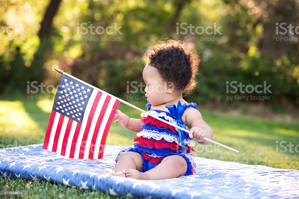 Baby Girl Sitting and Holding American Flag stock photo