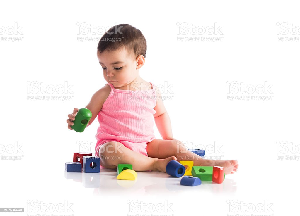 Baby girl sitting and playing with blocks stock photo