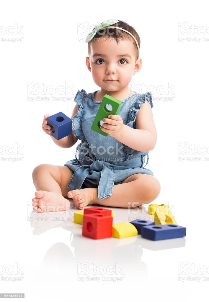 Baby girl sitting and playing with toys - foto de stock