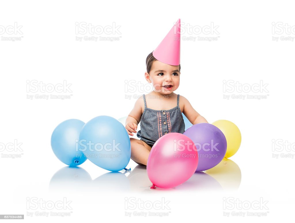Baby girl sitting and smiling with party decoration - foto de stock