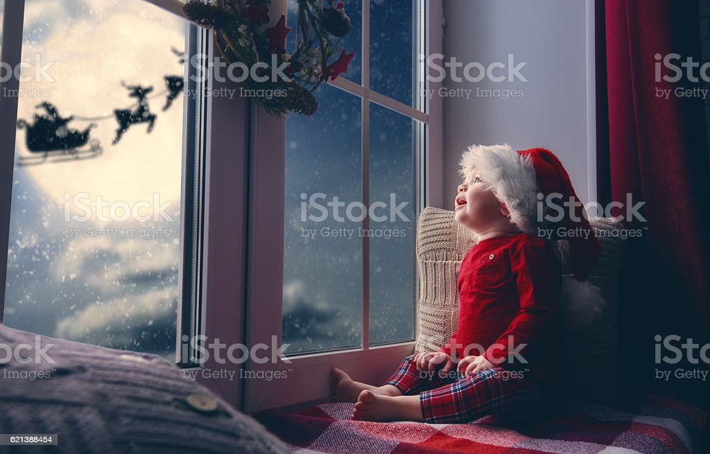 baby girl sitting by the window stock photo
