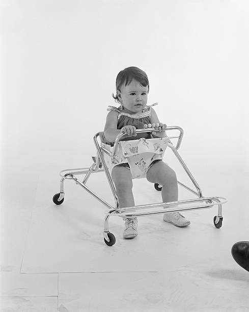 Baby girl sitting in baby walker stock photo