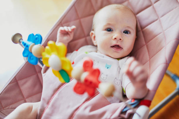 Babymädchen in Wippe sitzen und spielen mit bunten Spielzeug – Foto