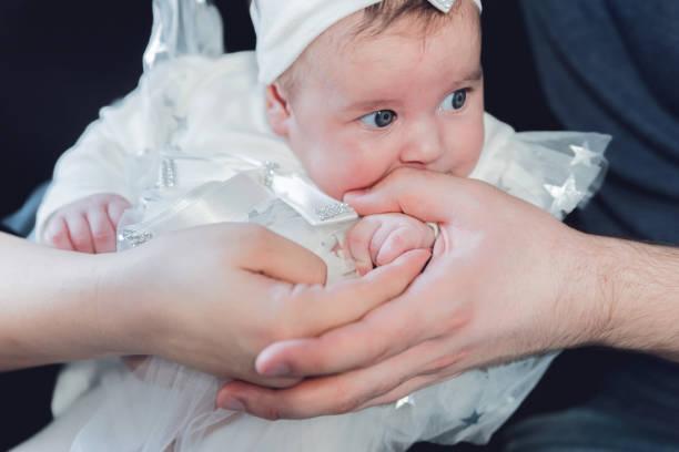 niña sentada en el regazo de los padres - bautizo fotografías e imágenes de stock