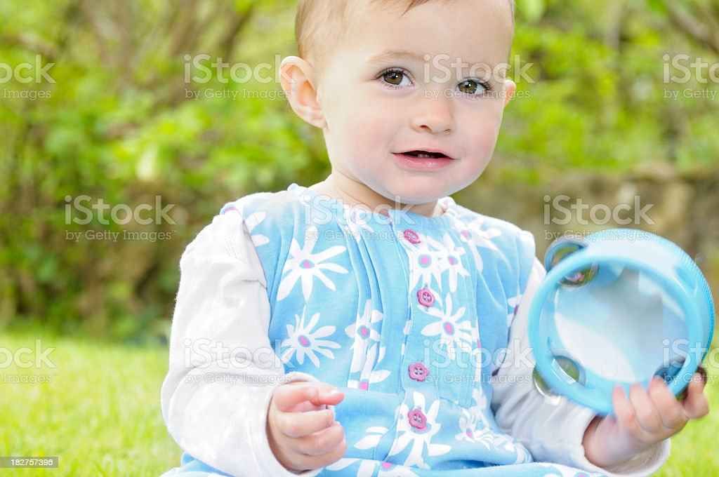 Baby Girl Sitting In The Garden/Park Holding A Tambourine royalty-free stock photo