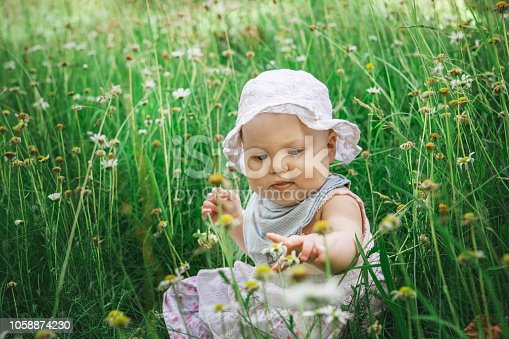 Baby girl sitting in the green grass.