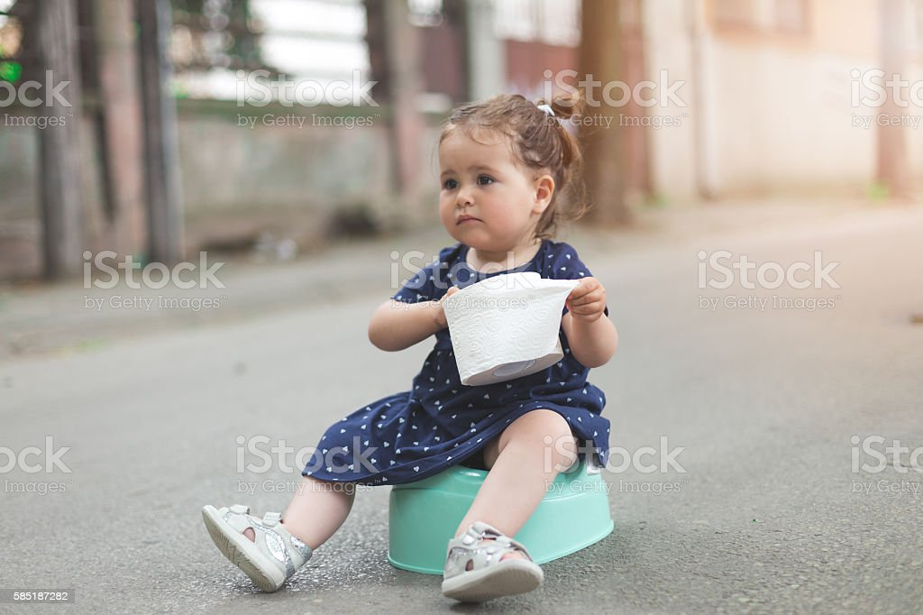 baby girl sitting on a potty outdoors ,holding toilet paper stock photo