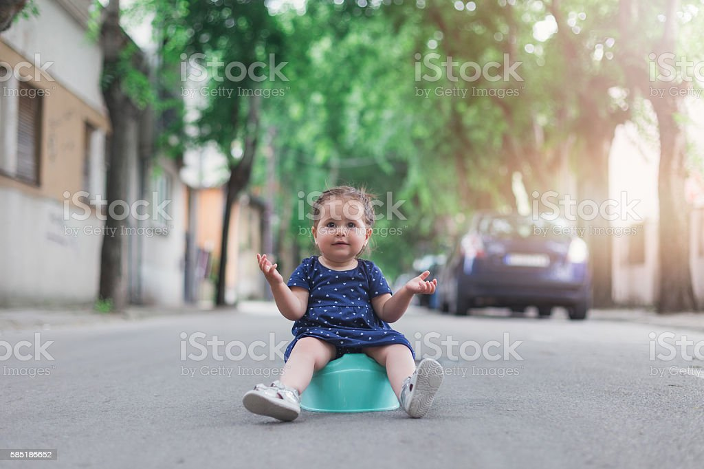 baby girl sitting on a potty outdoors stock photo
