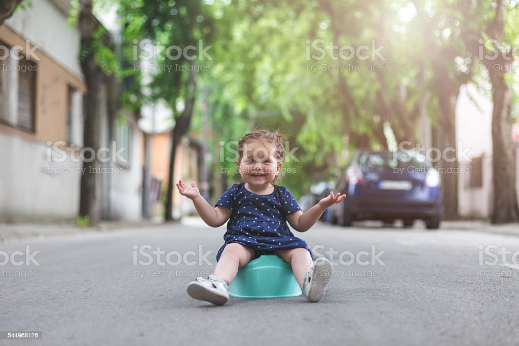 baby girl sitting on a potty outdoors spread hands stock photo