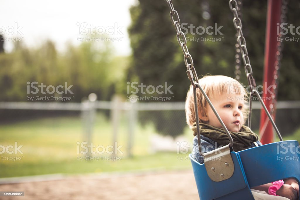 Baby girl sitting on a swing royalty-free stock photo
