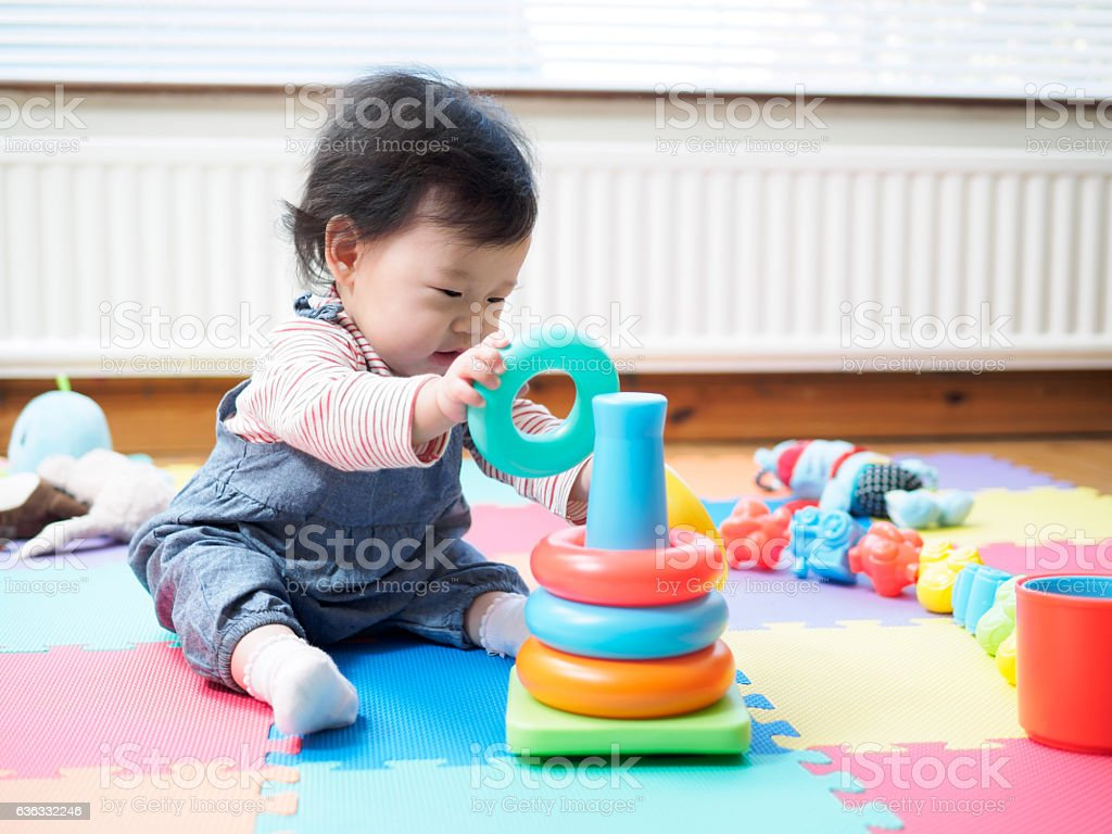 baby girl sitting on play mat  and playing toy stock photo