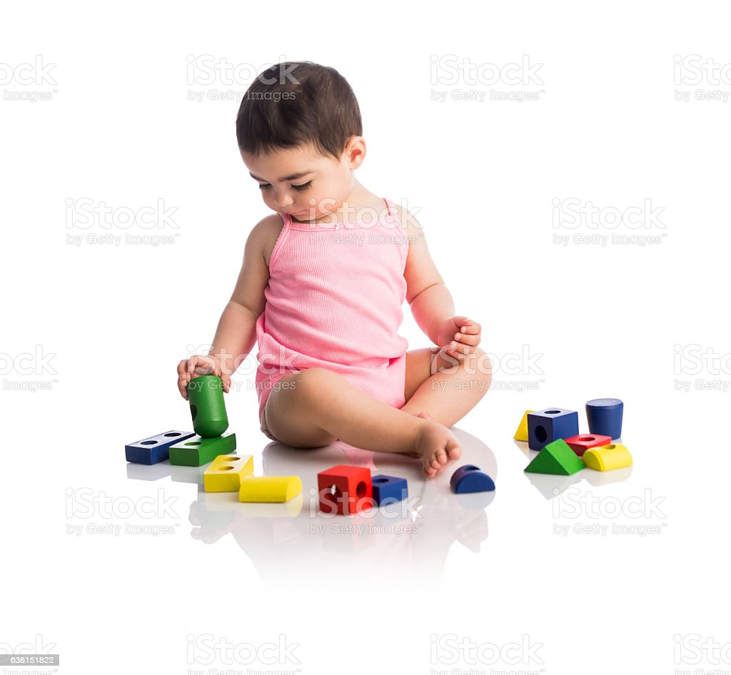 Baby girl sitting with toy blocks and playing - foto de stock