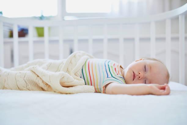 Baby girl sleeping in co-sleeper crib stock photo
