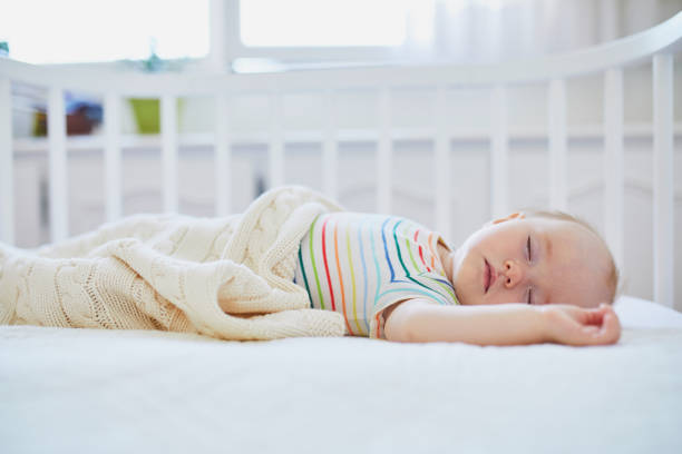 Baby girl sleeping in co-sleeper crib Adorable baby girl sleeping in co-sleeper crib attached to parents' bed. Little child having a day nap in cot. Infant kid in sunny nursery crib stock pictures, royalty-free photos & images