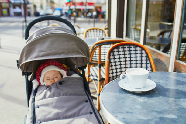Baby girl sleeping in pram on outdoor terrace of Parisian street cafe stock photo