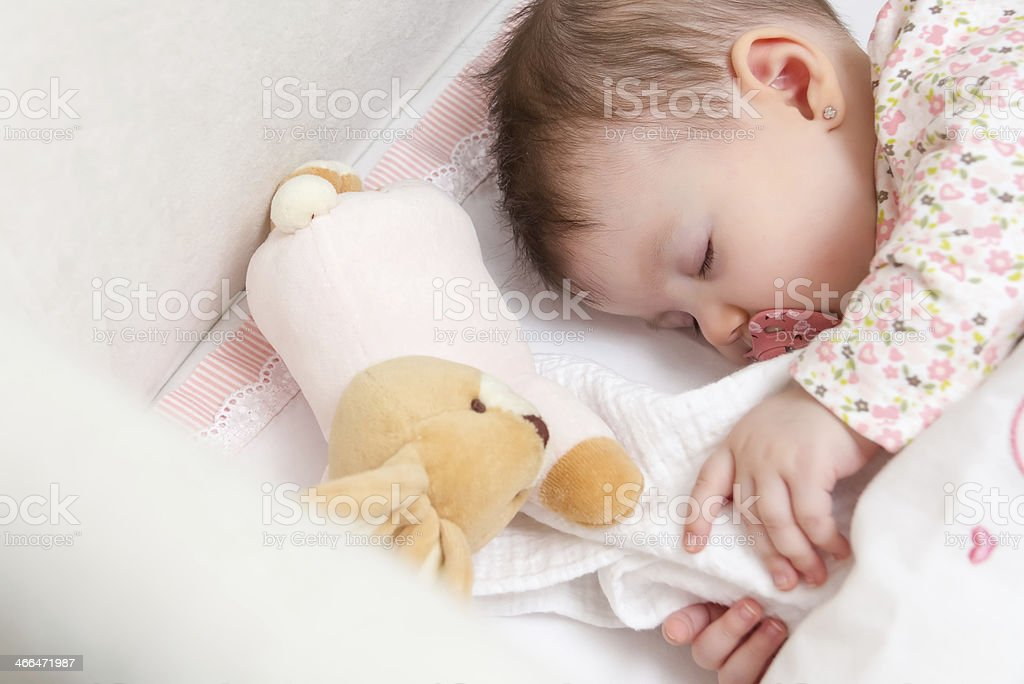 Baby girl sleeping with toy rabbit and pacifier stock photo