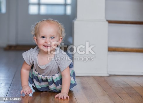 Beautiful Caucasian baby girl with blonde curly hair is smiling at the camera as she learns to crawl at home in family living room.