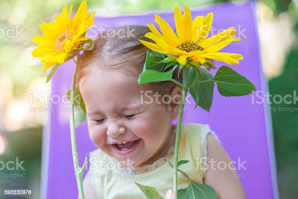 Photo of Baby girl smiling and playing with sunflowers