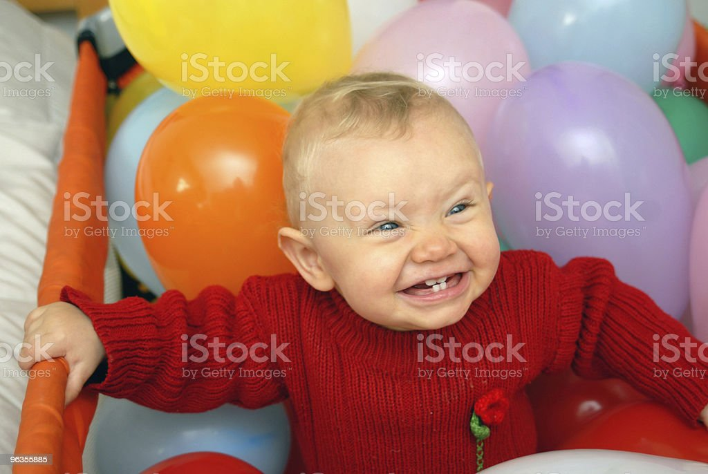 Baby girl smiling between multicolored balloons royalty-free stock photo