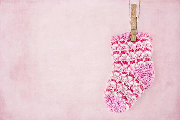 Baby girl socks on pastel pink background stock photo