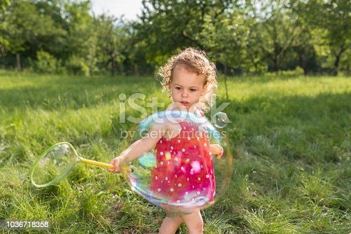 Baby girl playing with bubble wand while standing in park.