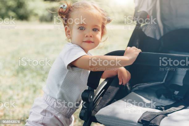 Baby girl standing near a baby carriage picture id958543576?b=1&k=6&m=958543576&s=612x612&h=ymqc8qs1a4o5wecyg08aeej8wmbefocvc7 uw1bey0w=