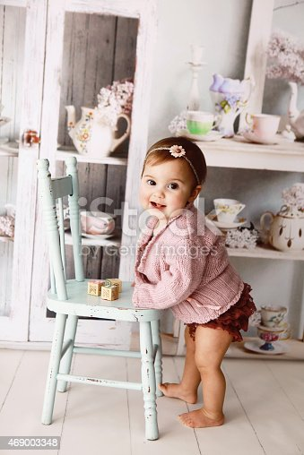istock Baby girl standing while holding a blue wooden chair 469003348